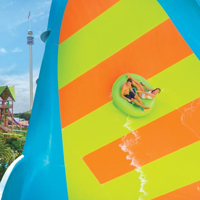 A man and a woman slide down Kare Kare Curl at Aquatica Orlando.