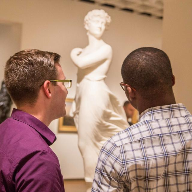 Guests regarding a marble sculpture inside the Orlando Museum of Art