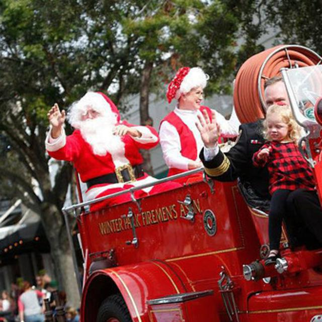 Santa rides a fire truck in the Winter Park Christmas Parade