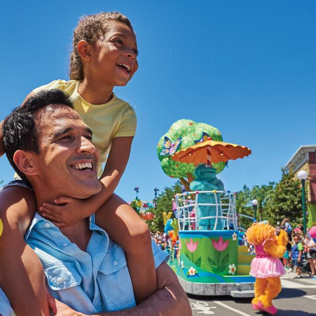 A beaming father with his daughter sitting on his shoulders as they watch the character parade in SeaWorld Orlando