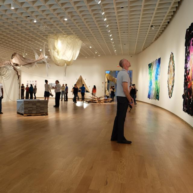 A man views art on a curved wall at an exhibition at Orlando Museum of Art.