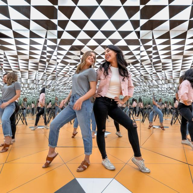 Guests pose for a photo inside the Infinity Room at Museum of Illusions in Orlando