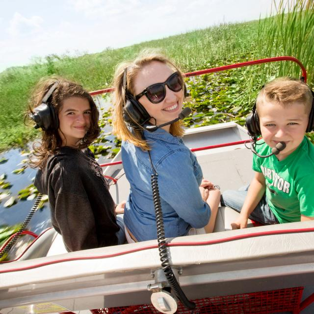 Spirit of the Swamp Airboat Rides mom and kids on airboat posing for camera