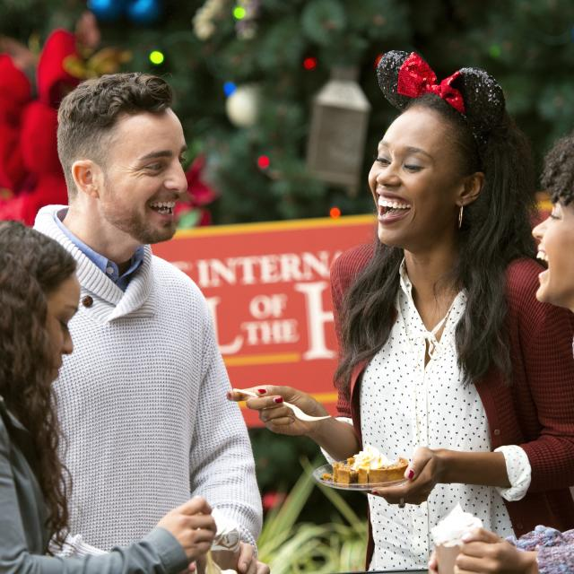A group of friends eating food and enjoying EPCOT International Festival of the Holidays.