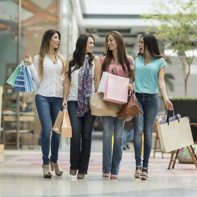 A group of women walking at a shopping center and holding bags