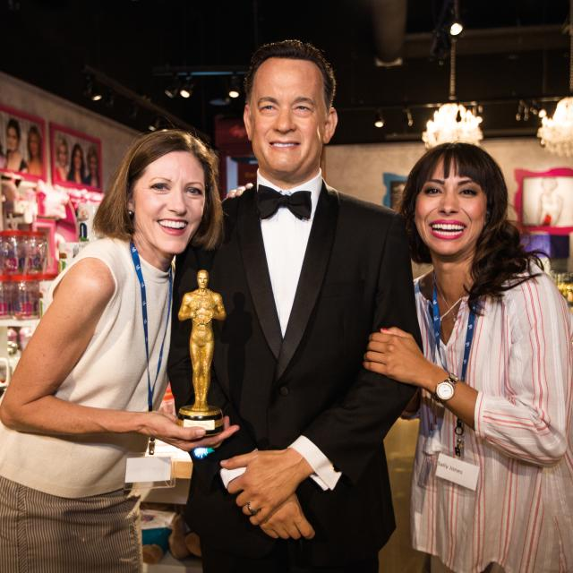 Two women posing with a wax figure of Tom Hanks at the Madame Tussauds attraction