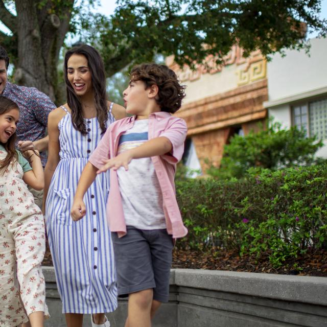 A family of four dancing outside in an Orlando theme park.