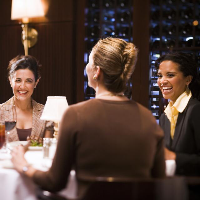A group of women laughing and dining at The Capital Grille - Mall at Millenia.