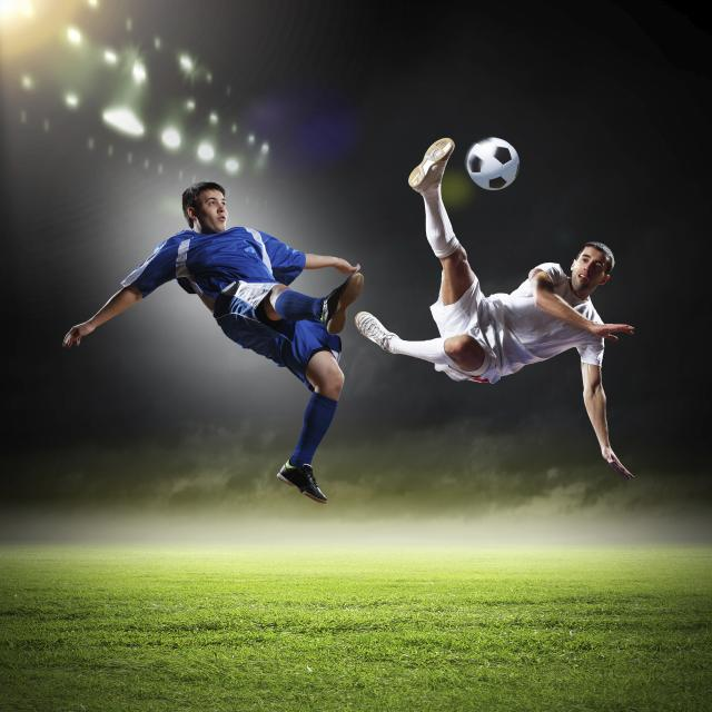 two soccer players going for the ball in the air