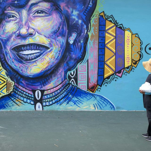 A woman views a large mural of Zora Neale Hurston in Eatonville