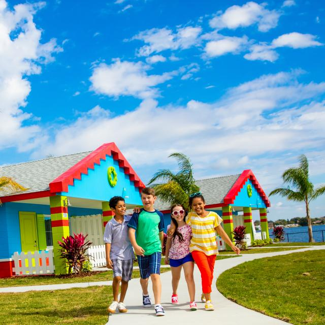 Kids walking in front of colorful LEGO bungalows, framed by palm trees, at LEGOLAND® Florida Resort.