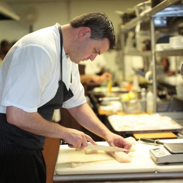 Chef James Petrakis preparing a dish in the kitchen at The Ravenous Pig restaurant