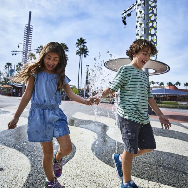 Siblings walking across a splash pad at Universal CityWalk Orlando