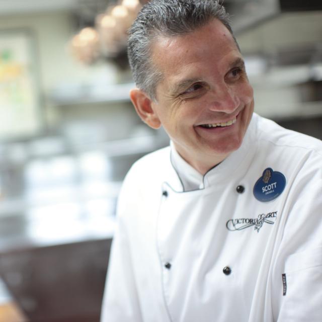Chef Scott Hunnel smiling in the kitchen of Victoria & Albert's restaurant.