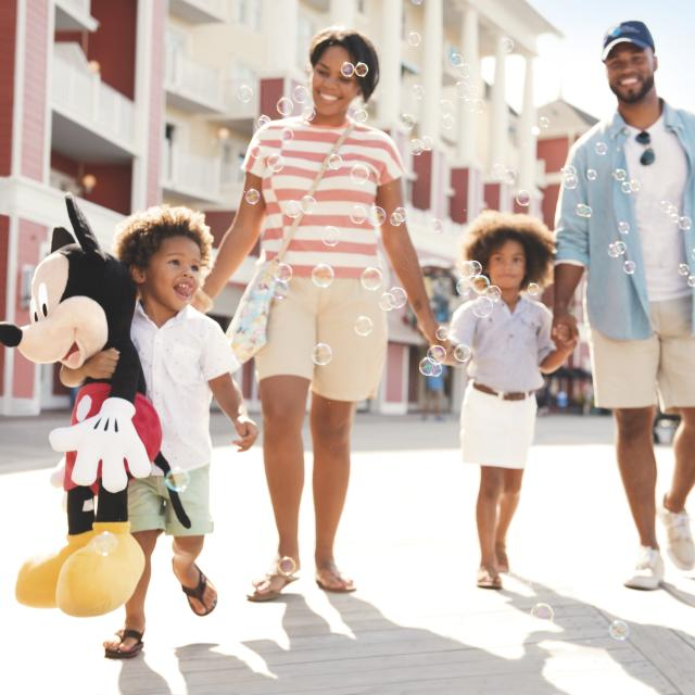 A family of four, with the youngest carrying a large Mickey Mouse plush toy walk by Disney's Boardwalk Inn.