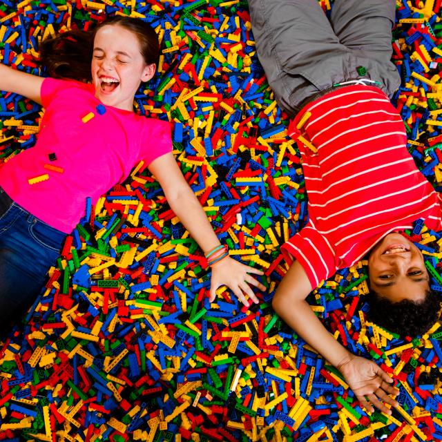 Two kids play on a bed of LEGO bricks at LEGOLAND® Florida Resort