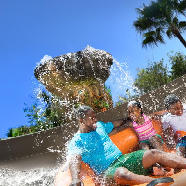 A family getting soaked by a waterfall on Miss Adventure Falls at Disney's Typhoon Lagoon Water Park