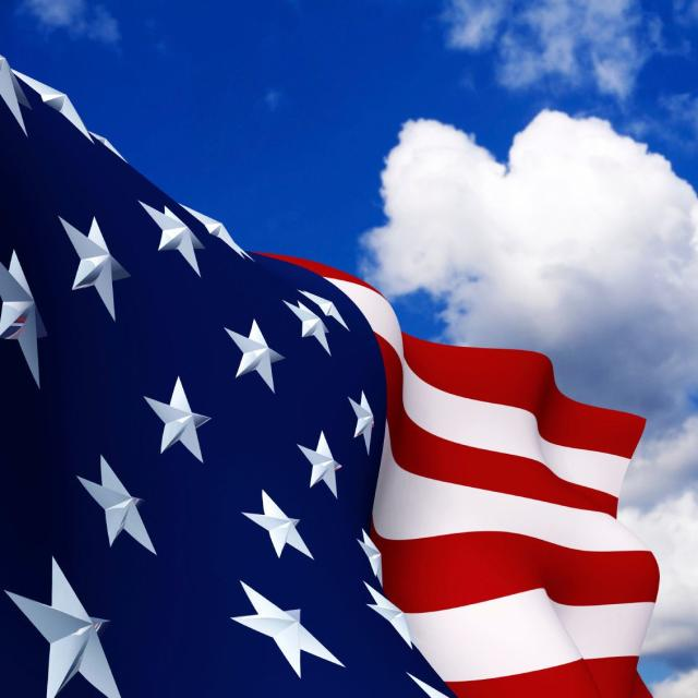 Closeup of an American flag with a blue sky background