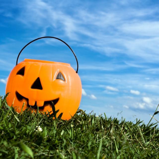 Plastic pumpkin candy holder sitting in the grass under blue skies.