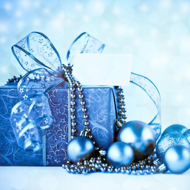 A Christmas present wrapped in blue paper with blue ornaments