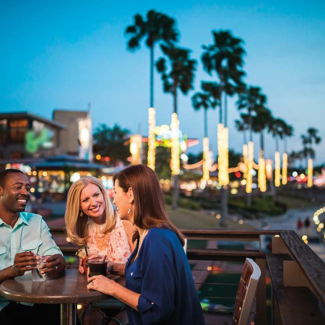 Three people sitting at a table, having drinks at Universal CityWalk at night