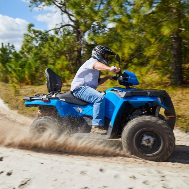 A man kicks up some dirt as he drives a blue ATV around the bend of a trail at Revolution Adventures.