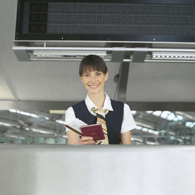 A customer service person working at an airport and holding a passport