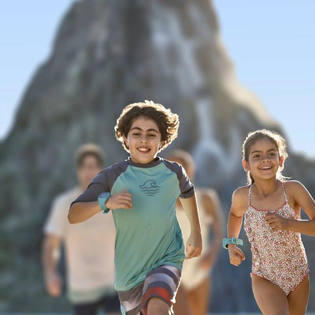 Kids in swim suits running ahead of their parents at Universal's Volcano Bay