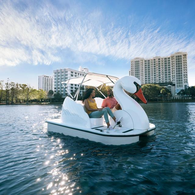A couple exploring Lake Eola on a swan boat