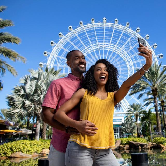 A couple posing for a selfie in front of The Wheel at ICON Park