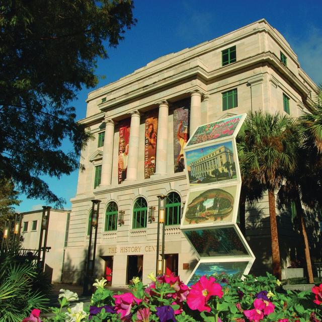 The exterior of the Orange County Regional History Center and Heritage Square, with flowers in the foreground.