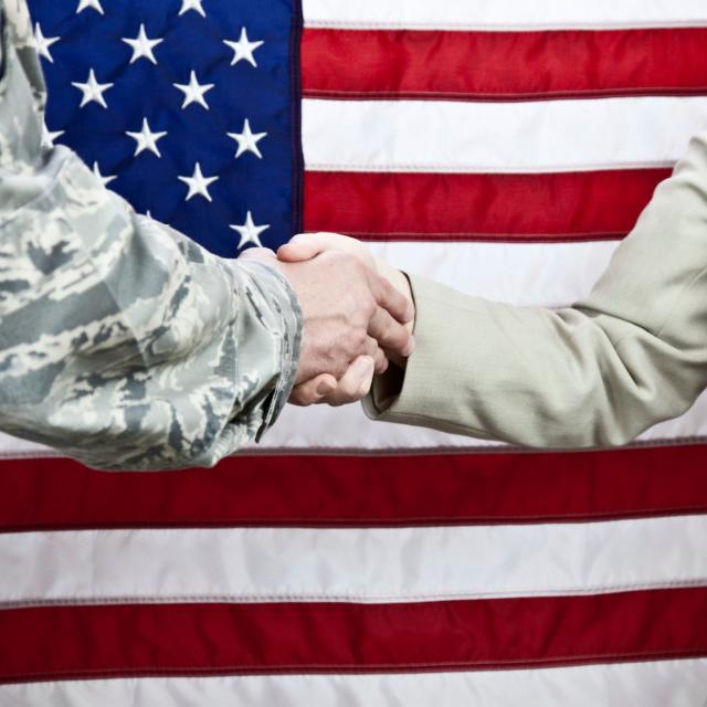 A handshake between a member of the miltary and a female civilian with an American flag background