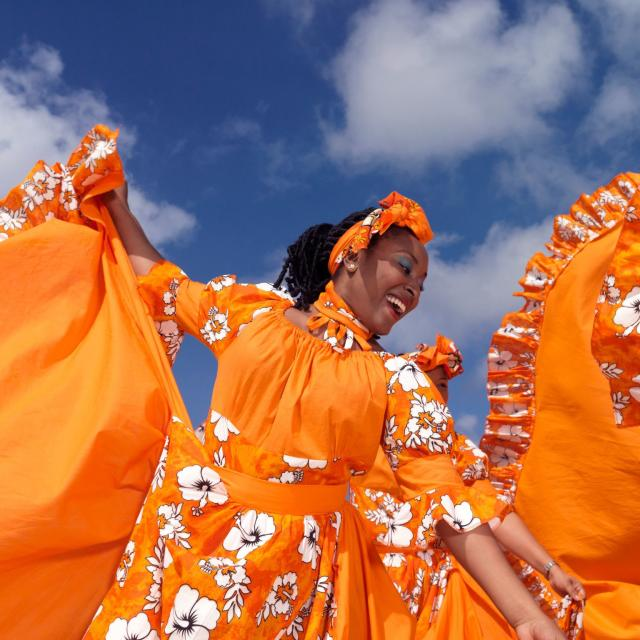 Caribbean dancing troupe wearing bright orange costumes perform on a beach.