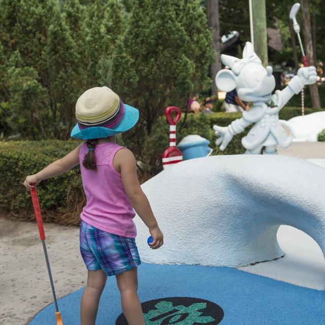 A little girl golfing at Disney's Winter Summerland Miniature Golf