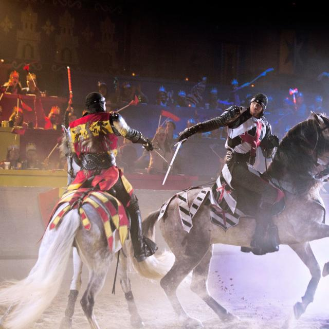 Two knights on horseback battle with swords at Medieval Times Dinner & Tournament