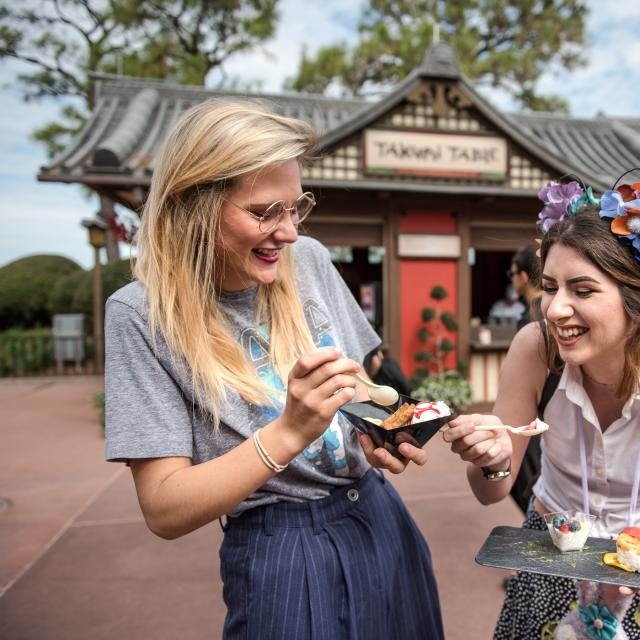 Two women enjoy food at the Epcot International Festival of the Arts