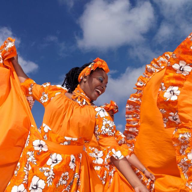 Caribbean dancing troupe wearing bright orange dresses as they perform on a beach.