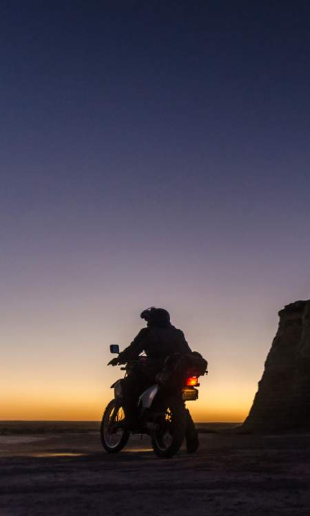 A motorcycle near Monument Rocks at dusk.