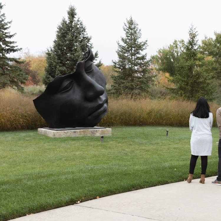 游客们带着Igor Mitoraj的月光——走出弗雷德里克梅杰花园和雕塑公园。
