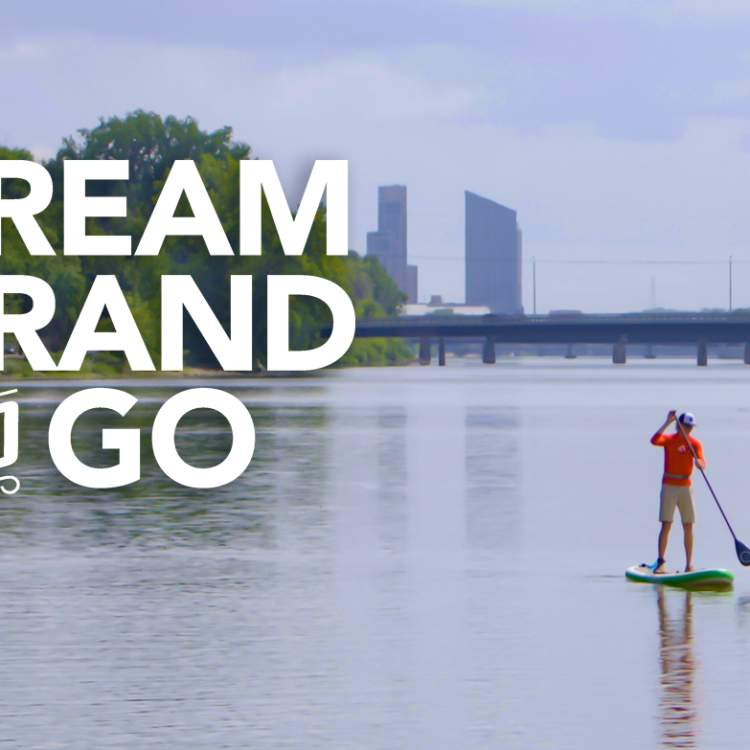 Dream Grand and Go logo with people stand-up paddle boarding in Grand Rapids.