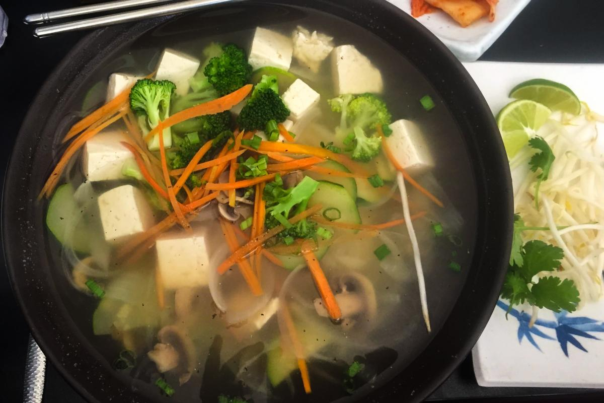 A bowl of tofu pho with toppings on the side.