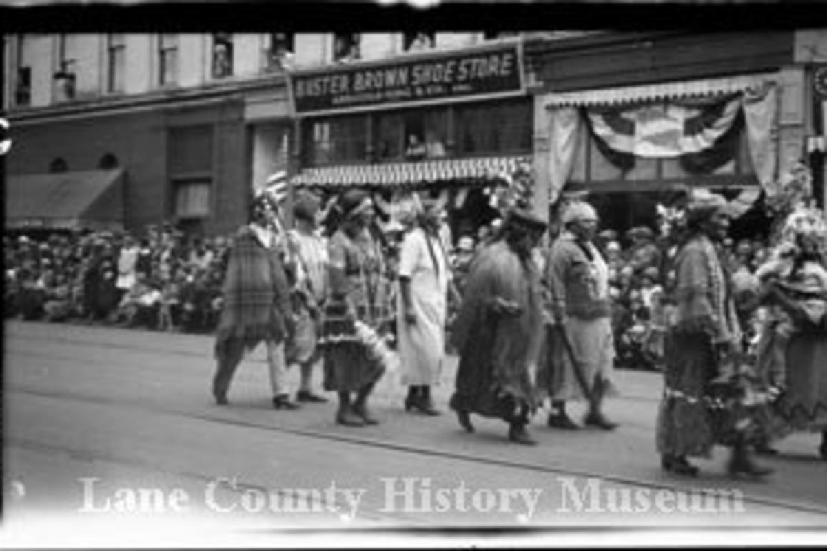 A black and white photo of Indigenous Peoples in regalia for a parade in 1926 down the streets of Eugene.
