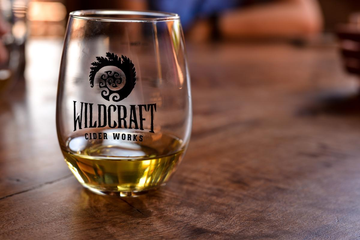 A tumbler glass is a third full of cider at Wildcraft Cider Works