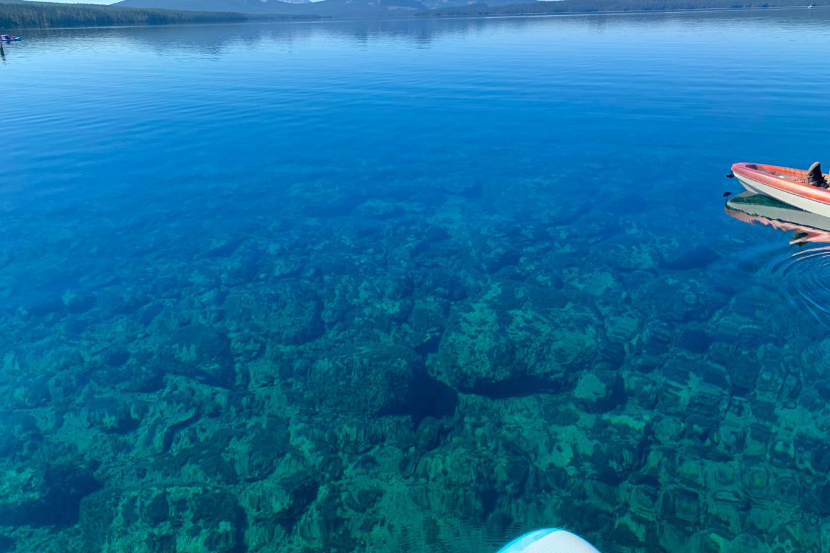 Watercraft floating on a crystal clear lake in the Cascade Mountains of Oregon.