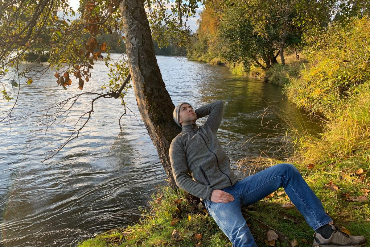 Man sits leaning against a tree beside the Willamette River with fall foliage surrounding him.