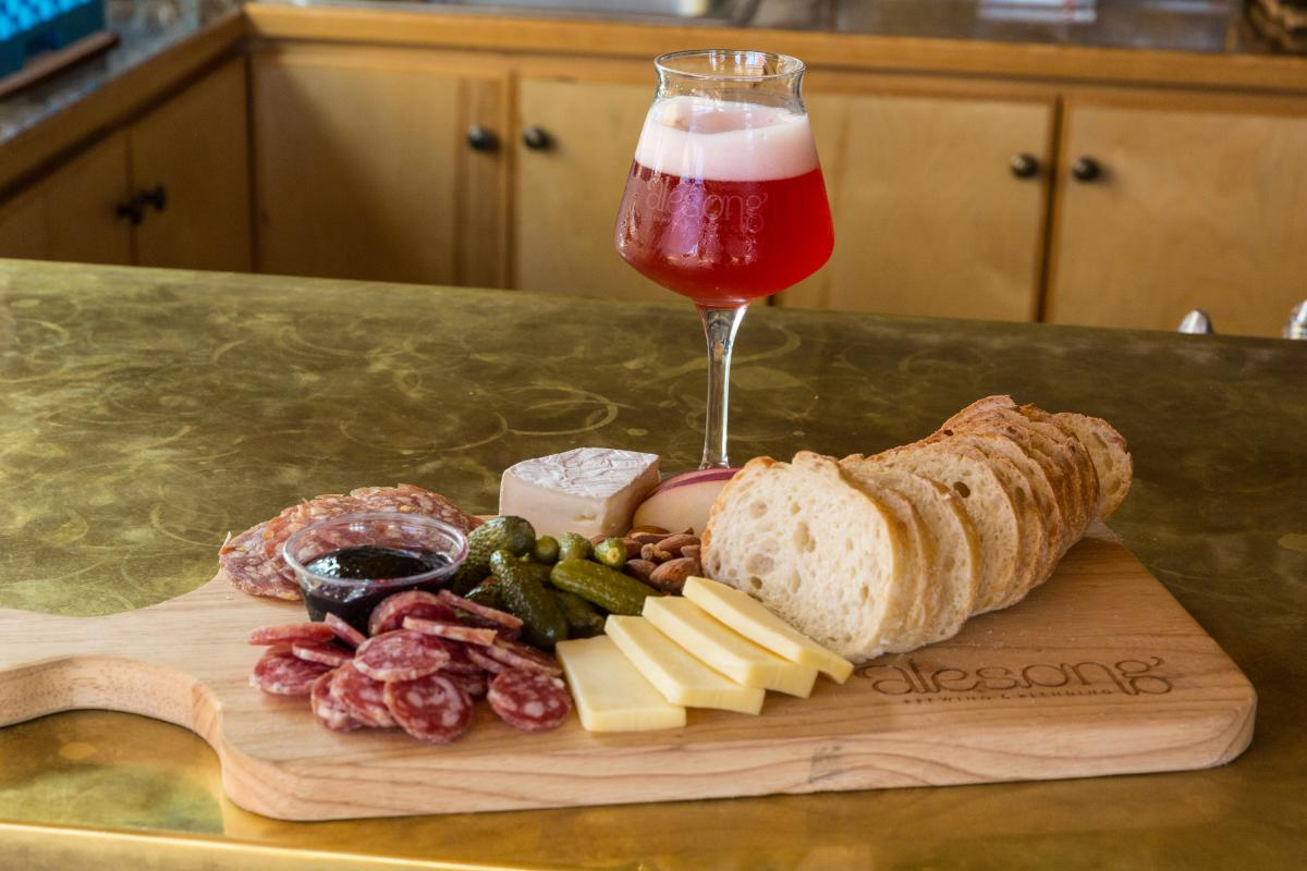 Alesong Brewing & Blending Glass of Beer with Bread and Cheese Plate.