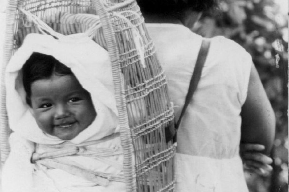 An Indigenous Siletz woman carries a smiling baby on her back in a woven cradleboard. Photo is black and white.