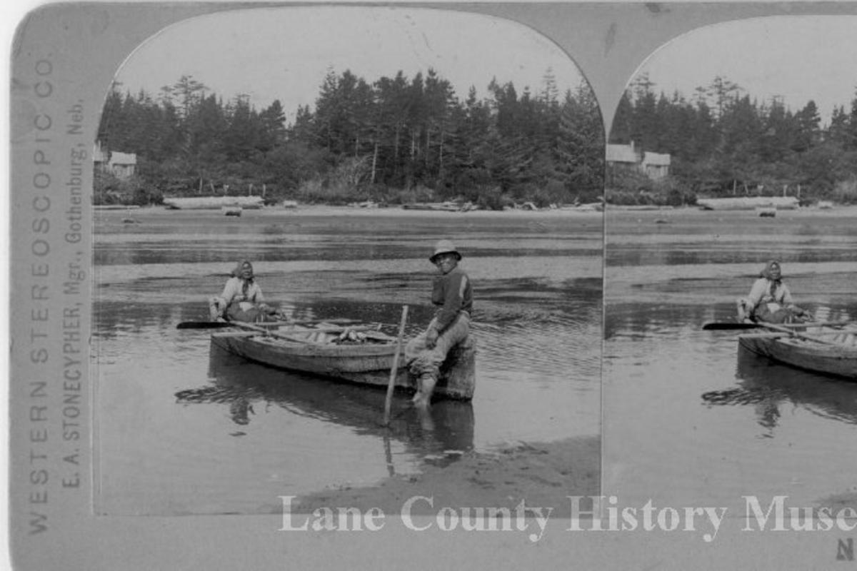 Native couple on a canoe in the Siuslaw River near Florence. Black and white historic photo from 1900s.