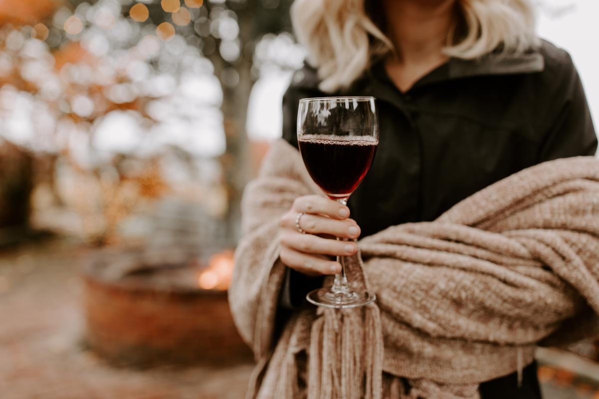 A hand holds a glass of red wine. There is a shawl wrapped around the arms of the person holding the wine glass. Fall foliage is in the background.