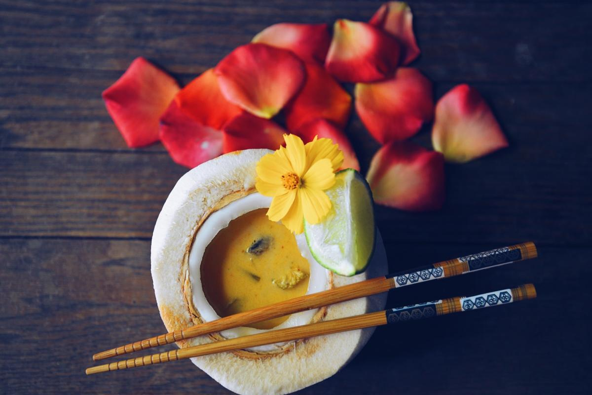 Tom Kha soup in a young coconut with lime, flowers and chopsticks in the scene.